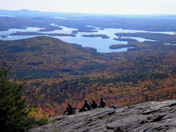 Hikers relaxing on the summit ledges of Mount Percival enjoy a bird's-eye view of nearby Squam Lake (photo by Mike Dickerman)
